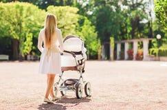 有婴儿推车的愉快的母亲在公园 免版税库存照片