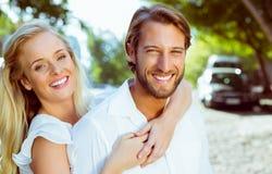拥抱和微笑对照相机的有吸引力的夫妇 免版税库存图片