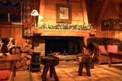 有木灼烧的壁炉的传统瑞士山中的牧人小屋客厅 免版税库存图片