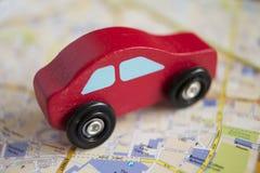 Κόκκινο ξύλινο αυτοκίνητο παιχνιδιών στον οδικό χάρτη Στοκ Φωτογραφίες