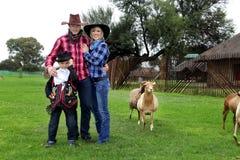 在绵羊农场的牛仔家庭 库存图片