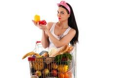 坐在超级市场台车的妇女 免版税库存图片