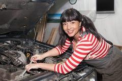 修理汽车的微笑的女工 库存照片
