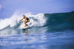 惊人的蓝色波浪的冲浪者女孩 免版税库存照片