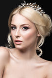 一个新娘的图象的美丽的白肤金发的女孩有一个冠状头饰的在她的头发 秀丽表面 背景镜象婚礼白色 免版税图库摄影