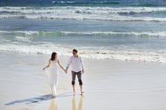 Жених и невеста держа руки приближает к морю в дне свадьбы Стоковые Изображения