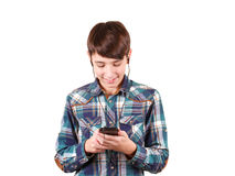 Εύθυμο αγόρι εφήβων στο πουκάμισο καρό που ακούει τη μουσική και που δακτυλογραφεί στο κινητό τηλέφωνο που απομονώνεται στο λευκό Στοκ φωτογραφία με δικαίωμα ελεύθερης χρήσης