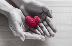 在手上的红色心形的丝绸 免版税库存图片
