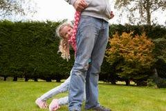 一起打比赛的父亲和女儿在庭院里 免版税图库摄影
