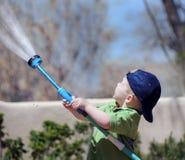 男孩庭院浇灌 免版税图库摄影