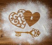 心脏和面粉的钥匙作为爱的标志在木背景的 重点 看板卡减速火箭的葡萄酒 免版税库存照片