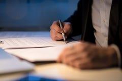 Επιχειρηματίας που απασχολείται αργά να υπογράψει ένα έγγραφο ή μια σύμβαση Στοκ εικόνες με δικαίωμα ελεύθερης χρήσης