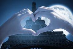 做心脏形状的手的综合图象在海滩 免版税库存图片