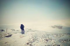 有大背包和雪靴的单独游人走在多雪的道路的使模糊 国家公园阿尔卑斯公园在意大利 老保守冬天天气 免版税库存图片