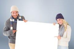 Σύνθετη εικόνα του ελκυστικού ζεύγους στη χειμερινή μόδα που παρουσιάζει αφίσα Στοκ εικόνα με δικαίωμα ελεύθερης χρήσης