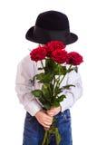 Ντροπαλό μικρό παιδί με τα κόκκινα τριαντάφυλλα Στοκ Φωτογραφία