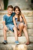 十几岁的男孩和女孩坐台阶在公园 免版税库存照片