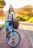 少妇坐在街道自行车车道的自行车 免版税库存照片