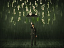 站立与在美金雨概念的伞的商人 免版税库存图片