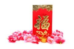 红色信封、鞋子型金锭(元鲍)和李子花 图库摄影