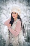 有白色毛皮盖帽的微笑的妇女和羊皮享受在森林侧视图的冬天风景愉快深色女孩摆在 免版税库存图片