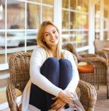 俏丽的微笑的妇女坐扶手椅子户外 免版税库存照片