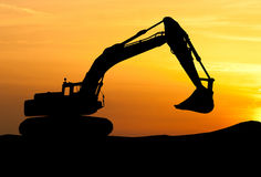 挖掘机装载者剪影在建造场所的有上升的 免版税库存照片