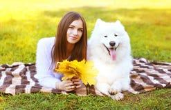愉快的俏丽的妇女和白色萨莫耶特人尾随获得乐趣户外 免版税库存图片