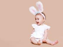 坐在服装复活节兔子的逗人喜爱的婴孩 免版税库存照片