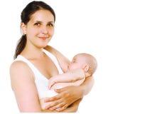 有睡眠婴孩的可爱的愉快的微笑的母亲 免版税库存照片