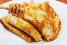 薄煎饼用在一块白色板材的蜂蜜糖浆 库存照片