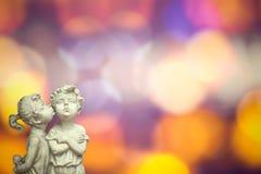 天使爱上被弄脏的华伦泰背景的夫妇雕象 免版税库存图片