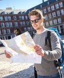 年轻学生背包徒步旅行者旅游看的城市地图在假日移动 免版税库存图片