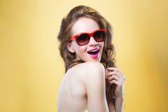 在金背景的有吸引力的惊奇的少妇佩带的太阳镜 免版税图库摄影