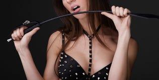 Сексуальная девушка в черной спиковой игре бюстгальтера с плеткой Стоковое Изображение