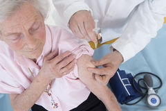Доктор впрыскивая вакцину к старшей женщине Стоковая Фотография RF