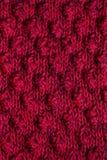 被编织的黑暗的桃红色围巾纹理  免版税库存图片