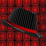 在抽象红色背景的现代浅顶软呢帽帽子 库存照片