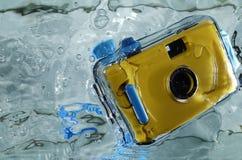 黄色防水照相机照片在水中与飞溅 免版税库存照片