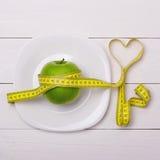 苹果计算机和厘米在板材 健身健康吃 免版税库存照片
