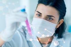 Закройте вверх ученого при трубка делая испытание в лаборатории Стоковая Фотография