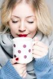 温暖的衣裳的白肤金发的妇女 免版税库存图片