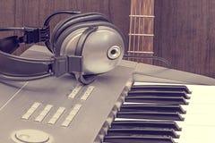 数字式密地键盘、耳机和声学吉他 免版税库存照片