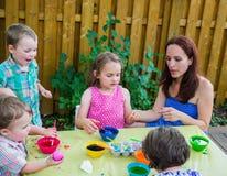绘复活节彩蛋的孩子外面与妈妈 免版税库存图片
