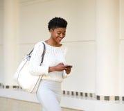 发在手机的微笑的妇女正文消息 免版税库存图片