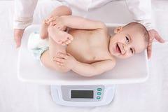 测量的微笑的美丽的舒适的矮小的婴孩 免版税库存照片