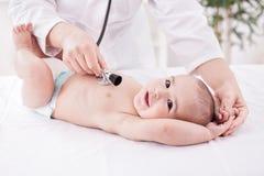 Женский педиатр доктора и терпеливый счастливый усмехаясь младенец ребенка Стоковая Фотография
