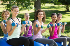 健身小组举的手重量在公园 免版税图库摄影