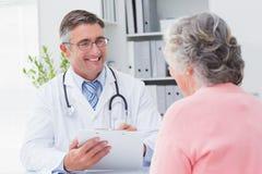 患者的微笑的医生文字处方 免版税库存图片