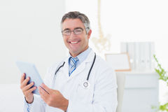 Уверенно мужской доктор используя планшет Стоковое Фото